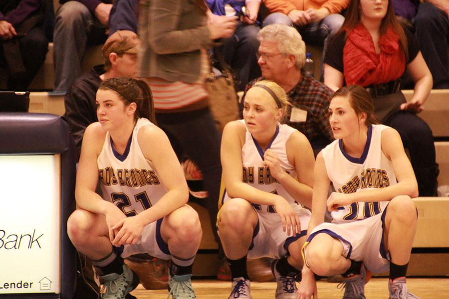From left, sophomore Robbi Ryan and seniors Molly Ligocki and Maddy McClure look to check into the basketball game.