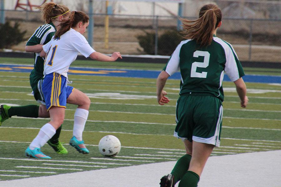 Sophomore Mackenzie Dougherty tries to dribble past a Kelly Walsh defender.