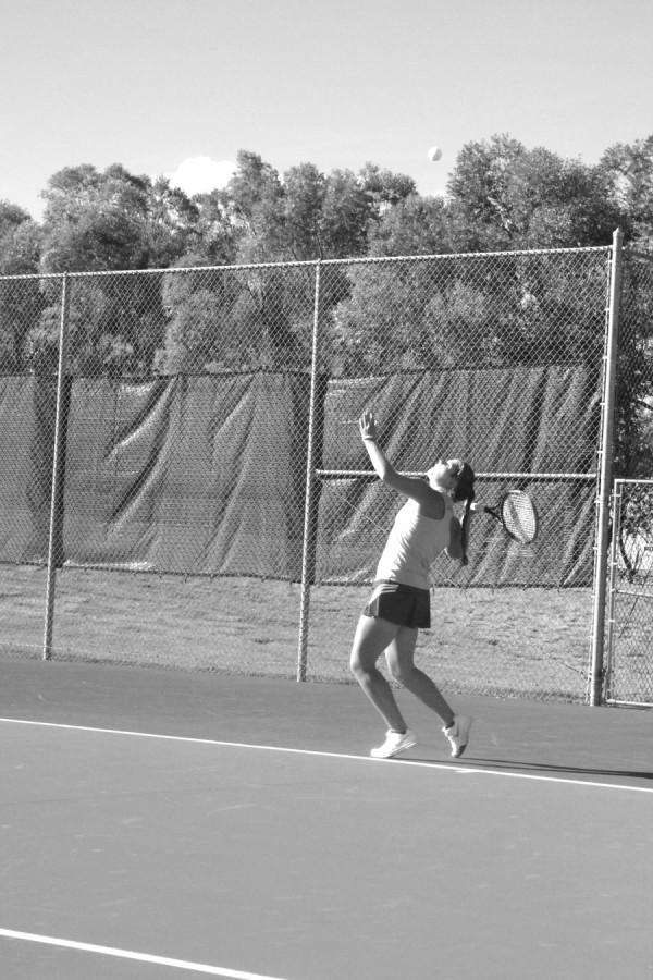 Senior Julia Fenn serves during a tennis match. Fenn is a four year state champion in number one singles tennis and her record is 58-0, undefeated in her high school career.