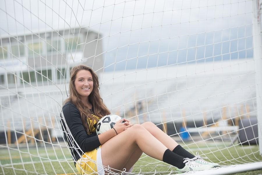 Senior Jamy Shassetz sits in the Homer Scott Field net with her soccer gear on. This will be Shassetz's fourth year playing on the varsity soccer team as a midfielder and defender.