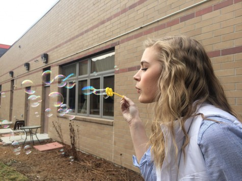 Gabrielle Golinvaux takes advice #10 and reminisces about her childhood by blowing bubbles in the Sheridan High School courtyard on a crisp Spring Day.