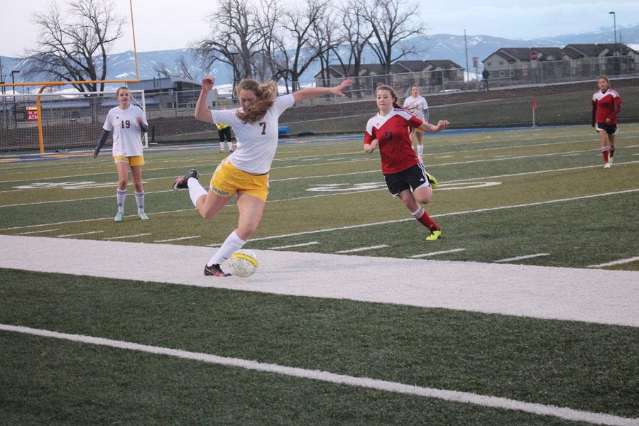 Freshman and varsity player Jordan Christensen kicks the across the field towards the opposing goal.