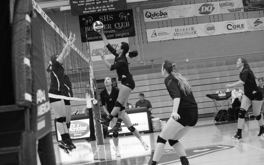 Mindy Songer spikes ball over net in high school volleyball game. (Photo courtesy Gretchen McCafferty)